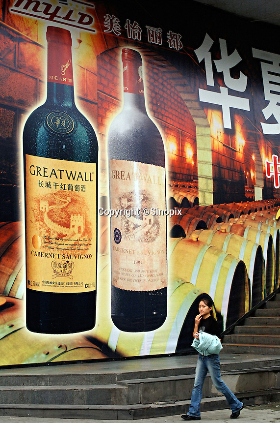 """A woman walking pass a large outdoor advert of Greatwall wine in Chengdu, China. Chengdu is the capital of China's most populous province, land-locked Sichuan. The capital city is seeing massive investment of capital as it has modelled itself as the gateway to the western China which the Chinese government are trying to encourage investement with its """"Go West"""" campaign.."""