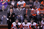 RIT's Head Coach Scott McDonald (far left) watches his player play. Princeton is winning 1-0 in the first period at Ritter Arena in Rochester, New York on October 19, 2012