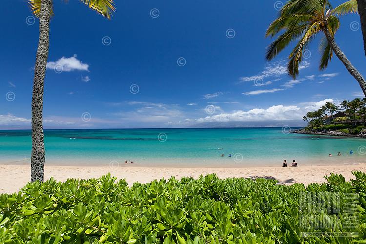 Visitors enjoying the turquoise water at Napili Bay, Maui.