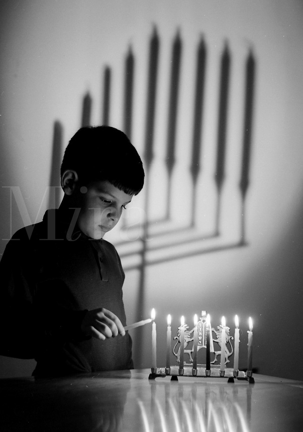 Boy lighting a Menorah at Chanuckah