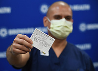 FORT LAUDERDALE, FL - DECEMBER 23: Miguel Pardo, RN shows off his COVID Vaccination Card after recieving his Moderna COVID-19 vaccine as Broward Health begins Vaccinating frontline Healthcare caregivers with the Moderna COVID-19 vaccine at Broward Health Medical Center Imperial Point on December 23, 2020 in Fort Lauderdale, Florida. <br /> CAP/MPI04<br /> ©MPI04/Capital Pictures