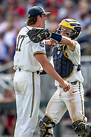 Michigan Wolverines pitcher Jeff Criswell (17) celebrates closing out Game 1 with catcher Joe Donovan (0) during the NCAA College World Series against the Texas Tech Red Raiders on June 15, 2019 at TD Ameritrade Park in Omaha, Nebraska. Michigan defeated Texas Tech 5-3. (Andrew Woolley/Four Seam Images)