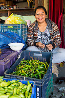 Punakha, Bhutan.  Young Woman Selling Chili Peppers in the Lobeysa Market.