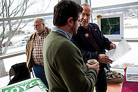Tony Donovan (right), president of the Maine Rail Transit Coalition, speaks with Damon Yakovleff of Portland (front) before the Portland Democratic City Committee town caucus in the East End School cafeteria in Portland, Maine, USA, on March 3, 2014. Donovan's group advocates for the return of passenger rail to a railroad owned by the state of Maine. Candidates presented their positions to the public and also gathered signatures required to get them listed on the ballot. The town caucus had speeches from various other local candidates and also served to choose delegates for the 2014 Maine State Democratic Caucus.