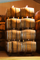 Rows of oak barrels stacked four high with fermenting wine. Giraud is specialised in oak aging champagne. A ray of sunshine shining through the roof illuminating the barrels Champagne house Maison Giraud-Hemart, also called Champagne Henri Giraud, Ay, Vallée de la Marne, Champagne, Marne, Ardennes, France, low light grainy grain