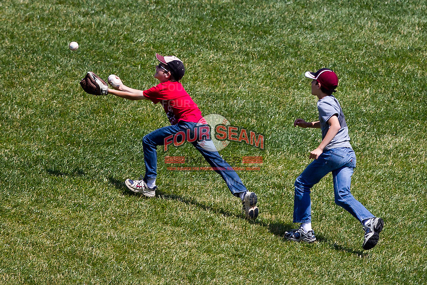 Two young fans try to catch a foul ball during a game between the Evansville Purple Aces and the Indiana State Sycamores in the 2012 Missouri Valley Conference Championship Tournament at Hammons Field on May 23, 2012 in Springfield, Missouri. (David Welker/Four Seam Images)