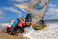 Brazilian fishermen (jangadeiros) push their boat towards the ocean on the beach of Prainha, Ceará state, northeastern Brazil, 8 March 2004. Jangadeiros, working on a unique wooden raft boat called jangada, keep the tradition of artisan fishing for more than four hundred years. However, being a fisherman on jangada is highly dangerous job. Jangadeiros spend up to several days on high-sea, sailing tens of kilometres far from the coast, with no navigation on board. In the last two decades jangadeiros have been facing up the pressure from motorized vessels which use modern, effective (and environmentally destructive) fishing methods. Every time jangadeiros come back from the sea with less fish.