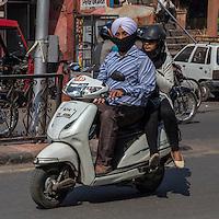 Jaipur, Rajasthan, India.  Mid-day Street Traffic in Central Jaipur.  Sikh Motorbike Driver and Passenger.
