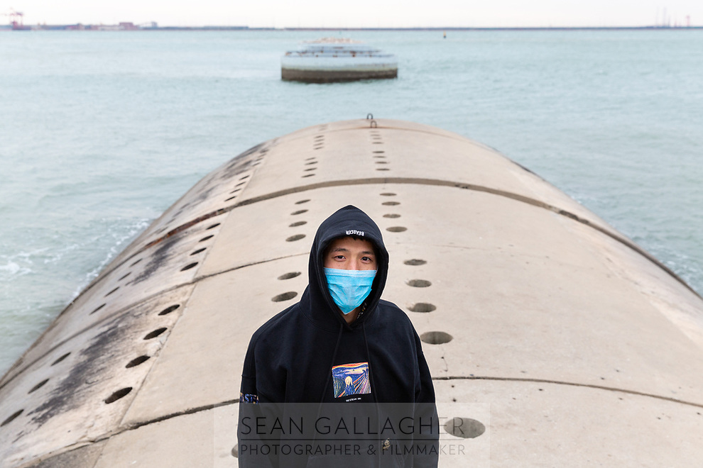 """A masked man stands on a seawall in the port city of Tianjin, in north-east China. Much of the port has been built on reclaimed land and now serves as one of China's busiest maritime hubs. According to an article in the South China Morning Post, """"Artificial seawalls now stretch along some 60 per cent of the mainland's coastline...destroying or severely disrupting the natural function of lush wetland, much of which is earmarked for reclamation. This increases pollution that threatens water bird populations, degrades inshore and oceanic environments, and leaves coastal populations more vulnerable to extreme weather events such as typhoons."""" As sea levels are predicted to rise in northern China, sea walls will be the first line of defence for the people in Tianjin, however severe storm surges have the potential to threaten these defences. Behind the sea walls, land subsidence in areas of the city is also adding to the threat of flooding, leading experts to warn of lingering dangers to the city's 11,000,000 residents."""