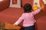 16 month old toddler girl finding ball hidden behind couch cushions