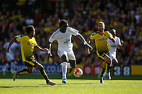 Bafetimbi Gomis of Swansea chased by Ikechi Anya of Watford and Valon Behrami of Watford   during the Barclays Premier League match Watford and Swansea   played at Vicarage Road Stadium , Watford