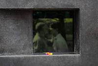 Am 27. Januar 2016 wurde der Tag des Gedenkens an die Opfer des Nationalsozialismus begangen. Anlass ist der 71. Jahrestag der Befreiung des Konzentrationslagers Auschwitz. Der Lesben- und Schwulenverband Berlin-Brandenburg (LSVD) und die Stiftung Denkmal fuer die ermordeten Juden Europas fuehrten aus diesem Grund eine Gedenkfeier am Denkmal fuer die im Nationalsozialismus verfolgten Homosexuellen in Berlin-Tiergarten durch. An der der Gedenkveranstaltung nahmen neben dem LSVD und der Stiftung Denkmal fuer die ermordeten Juden Europas auch Politiker aller im Bundestag vertretenen Parteien teil.<br /> Im Bild: Ein Teilnehmer hat ein Armband in Regenbogenfarben in dem Denkmal abgelegt. Im Hintergrund laeuft ein Film mit einer Szene in der sich zwei Maenner kuessen.<br /> 27.1.2016, Berlin<br /> Copyright: Christian-Ditsch.de<br /> [Inhaltsveraendernde Manipulation des Fotos nur nach ausdruecklicher Genehmigung des Fotografen. Vereinbarungen ueber Abtretung von Persoenlichkeitsrechten/Model Release der abgebildeten Person/Personen liegen nicht vor. NO MODEL RELEASE! Nur fuer Redaktionelle Zwecke. Don't publish without copyright Christian-Ditsch.de, Veroeffentlichung nur mit Fotografennennung, sowie gegen Honorar, MwSt. und Beleg. Konto: I N G - D i B a, IBAN DE58500105175400192269, BIC INGDDEFFXXX, Kontakt: post@christian-ditsch.de<br /> Bei der Bearbeitung der Dateiinformationen darf die Urheberkennzeichnung in den EXIF- und  IPTC-Daten nicht entfernt werden, diese sind in digitalen Medien nach §95c UrhG rechtlich geschuetzt. Der Urhebervermerk wird gemaess §13 UrhG verlangt.]