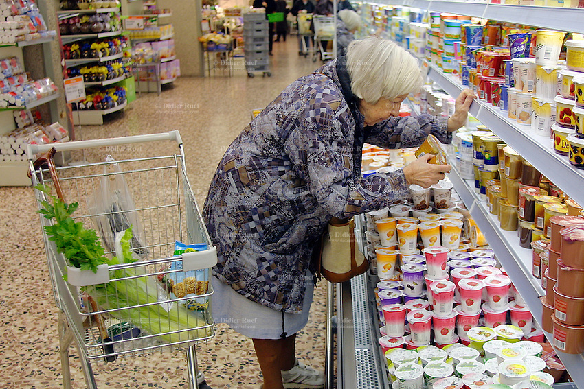 Switzerland. Ticino. Cassarate. Shopping at the Migros supermarket. An old woman looks at the quality of the dairy products counter ( yoghurt,..). Cassarate is just outside Lugano. Cassarate is just outside Lugano. 12.03.03 © 2003 Didier Ruef