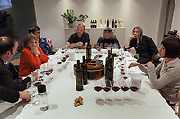 Switzerland. Canton Ticino. Cagiallo. Merlot wine testing for the new Magnificents' 17. Left to right: Nicolas Wüstti, Christine Crisci, Renaud Favre, Sacha Pelossi (L), the Gotthard musicians Leo Leoni, Nic Maeder and Freddy Scherer, Valentina Andrei. On the table, among wine bottles and glasses, a guitar Gibson Super Jumbo, SJ-200, belonging to Leo Leoni. The Swiss rock band Gotthard is associated with winemakers Valentina Andrei (Merlot Ivresse from Valais) and Sacha Pelossi (Merlot from Ticino) to create the new assemblage (50-50 from both winemakers) for a unique vintage bottle: Magnificents' 17. Gotthard is a Swiss hard rock band founded in Lugano by Steve Lee and Leo Leoni. Their last eleven albums have all reached number 1 in the Swiss album charts, making them one of the most successful Swiss acts ever. With 2 million albums sold, they managed to get multi-platinum awards in different parts of the world. Cagiallo is a village and and is part of the Capriasca municipality. 25.03.2019 © 2019 Didier Ruef