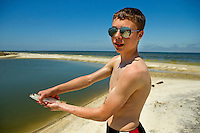 A teenage boy shows off his catch on Dauphin Island, Alabama, a barrier island located three miles south of the mouth of Mobile Bay in the Gulf of Mexico. This island, which is approximately 14 miles long and less than two miles wide, appears to have fully recovered from the impact of Hurricane Katrina (2005) and the BP Deepwater Horizon Oil Spill in 2010. Both events greatly reduced tourism income (fewer people came to the island) and local business owners say many establishments went out of business. Today they say they're looking forward to a rebounding tourism business.