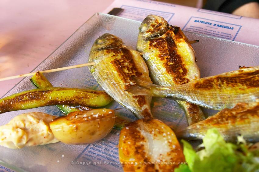 Gruissan village. La Clape. Languedoc. Restaurant La Cranquette. Grilled fried Saucanelles baby-dorade seabream on a skewer. France. Europe.