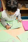 Education Preschool 4 year olds girl writing her name on artwork