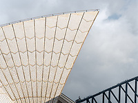 The Sydney Opera House is one of the world's most identifiable images.  This is an up close and personal view of the abstract roof lines and bridge in the background.  Tourists walking on top of the bridge are visible on the girders.