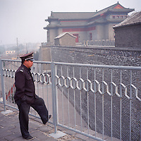 A Chinese security guard watches over the remnants of the Beijing city wall in October 2011.