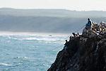 Fishermen fishing on the cliffs of Bordeira in the Algarve region of Portugal.