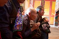 Tibetan pilgrims in the Upper Wutan Monastery, Rebgong (Chinese name - Tongren),  on the Qinghai-Tibetan Plateau. China.