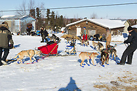 Volunteeers at the Shageluk checkpoint help Paul Johnson turn his team around from its parking spot on Saturday during Iditarod 2011