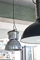 The living area is lit by a pair of mismatched industrial style pendant lamps