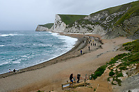 BNPS.co.uk (01202 558833)<br /> Pic: Graham Hunt/BNPS<br /> <br /> What a difference a year makes..<br /> <br /> The windswept beach at Durdle Door in Dorset is virtually deserted today, exactly a year after glorious weather saw thousands flock to the iconic landmark. <br /> <br /> A few stragglers, wrapped up in hats and coats, braved the wind and rain to walk along the beach that became a magnet for sunseekers during last year's pandemic.<br /> <br /> Whilst last year saw temperatures into the mid-20s - way above the average for May - today the thermometer struggled to reach 10C.<br /> <br /> <br /> (This picture was taken on 20/5/21)