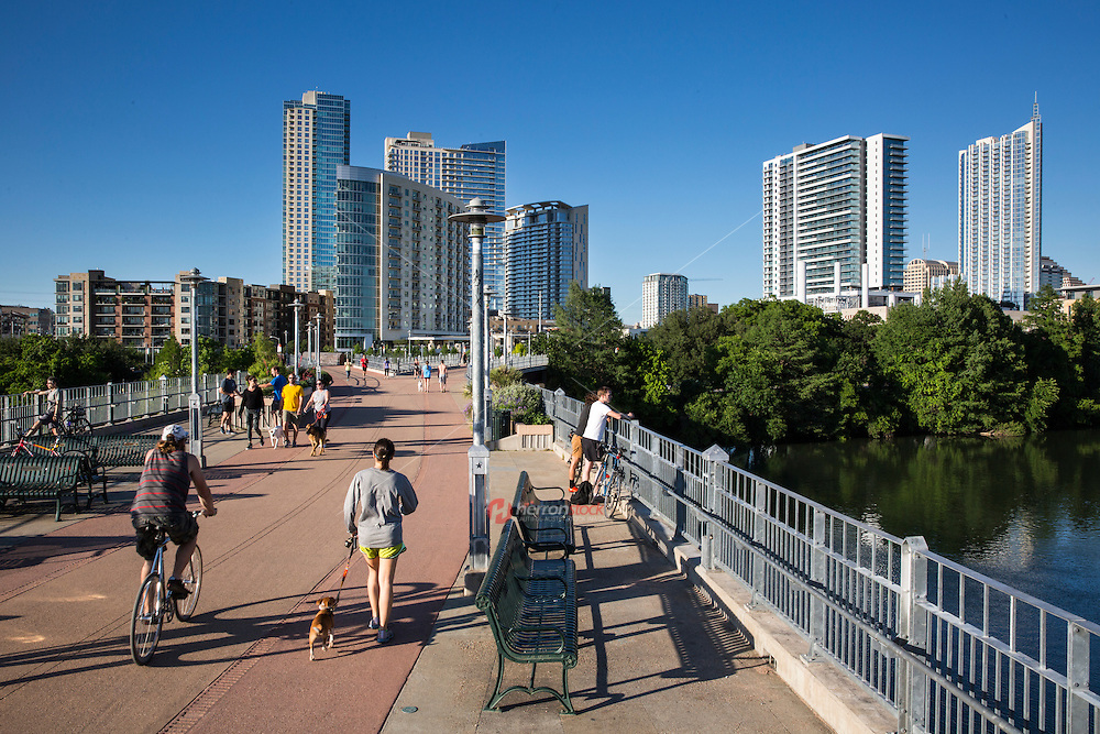 The Lamar Street Pedestrian Bridge is the central hub for the Lady Bird Lake Hike and Bike Trail. The bridge offers dog walking and lanes for bikers and runners to exercise with stunning views of Lady Bird Lake and the downtown Austin Skyline - Stock Image.
