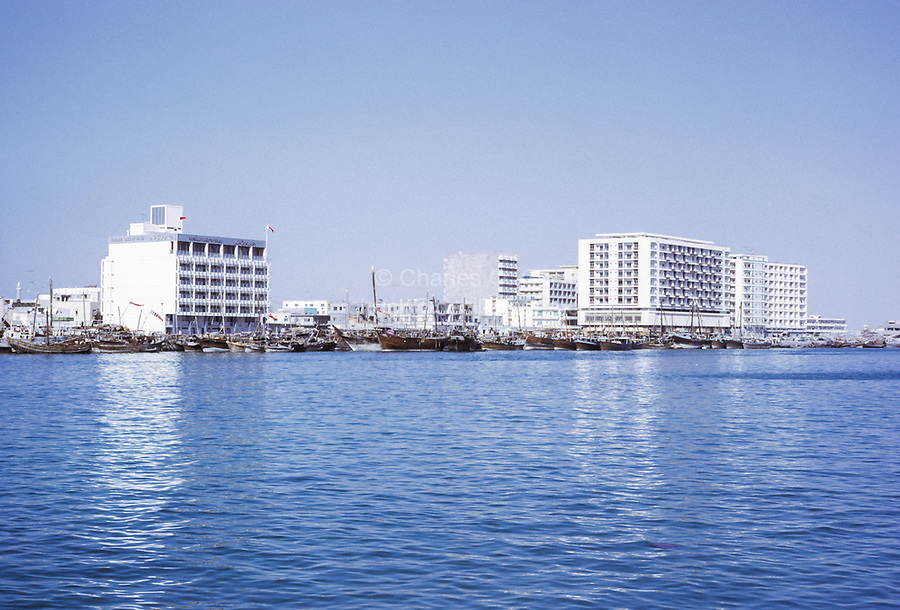 Dubai 1972, United Arab Emirates.  Dhows Line the Creek in front of National Bank of Dubai on left.  Other office and apartment buildings on right.