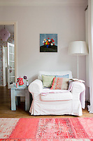 A cosy corner in the living room is furnished with a white armchair from Ikea and a colourful kilim rug