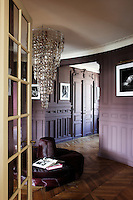 The circular banquette in the entrance hall has been upholstered in prune-coloured hide and the chandelier, designed by Stewart Haygarth, is made with pairs of spectacles