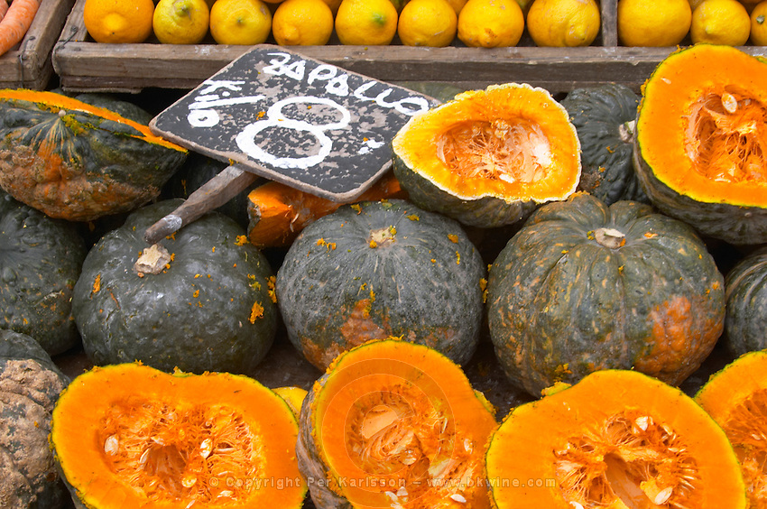 A market stall street market merchant selling pumpkins some cut in half to display the orange fruit flesh, Zapallo Montevideo, Uruguay, South America