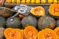 A market stall street market merchant selling pumpkins some cut in half to display the orange fruit flesh, Zapallo Montevideo, Uruguay, South America