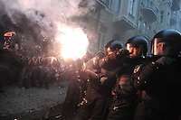 A protester light a smoke candle in the faces of a riot policemen deployment (Berkut) during the storm of the Kiev city council building, after  the Ukrainian  government's decision to stall on a deal that would bring closer ties with the European Union.