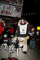Friday March 16, 2007  - Nome, Alaska ----  Dallas Seavey congratulaes part of his finishing 14-dog team after his arrival at the Nome burl arch finish line in 42nd place.