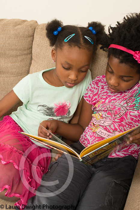 7 year old girl reading to 6 year old sister sitting on couch at home