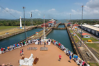 Panama Canal, Panama.  Passengers on Deck watch as Ship Transits Three Levels of the Gatun Locks en Route to Caribbean.  On Left, Container Ship Heads South.