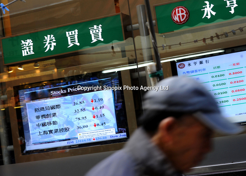 A passerby walks by Wing Hang Bank where a television screen indicates the stock prices .of the day and other relevant informations such as foreign currencies deposit rates, Hong Kong, China. Hong Kong has a mature and active foreign exchange market, the development of which has been stimulated by the absence of exchange controls and it's favorable time zone location. Hong Kong was the world's sixth largest foreign exchange market in terms of turnover..