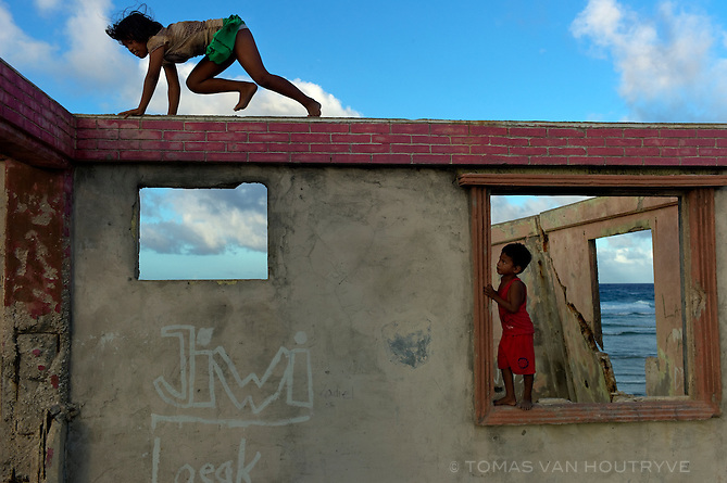 Children play in a partially destroyed abandoned home on the Pacific shore of Ebeye, Marshall Islands on June 16, 2012. Over 12,000 people live on the tiny overcrowded island of 36 hectares. The islanders relocated to Ebeye from their original homes because the U.S. military leases those areas for ballistic missile testing. Other current residents of Ebeye moved from islands which were contaminated by U.S. nuclear bomb tests. Infrastructure, housing and sanitation on Ebeye are deplorable.