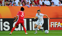 Heather O'Reilly (r) of Team USA and Ho Un Byol of Team North Korea during the FIFA Women's World Cup at the FIFA Stadium in Dresden, Germany on June 28th, 2011.