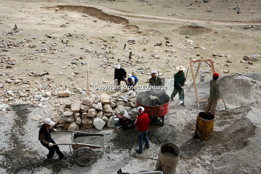 """China started building a controversial 67-mile """"paved highway fenced with undulating guardrails"""" to Mount Qomolangma, known in the west as Mount Everest, to help facilitate next year's Olympic Games torch relay./// Trucks and workers building the road to Everest Base Camp. <br /> Tibet, China<br /> July, 2007"""