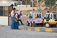 Tripoli, Libya, North Africa - Libyan Mother Waving to Daughter on Amusement Park Ride.
