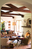 Under the massive beams of the ceiling an eclectic mix of furniture covered in various tones and textures of fabric create a feeling of comfort and warmth