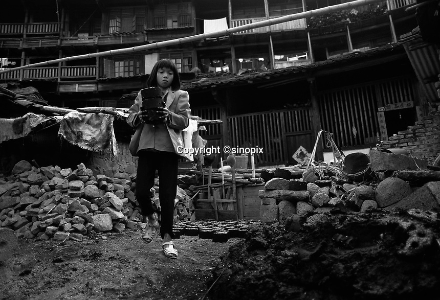 A young girl makes coal fuel bricks in Fujian Province, China.  Girls are often left out of school since they are married out of the family and country-side boys are given preference.<br /> May 1996<br /> <br /> photo by Richard Jones / Sinopix