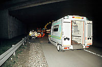 Ambulance paramedic crews attend a road treffic accident on the motorway. They are placing the injured driver onto a stretcher before taking her to hospital.
