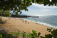 People enjoying Three Tables Beach near Pupukea, on Oahu's North Shore, seen through the trees