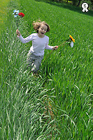Girl (7-8)  running through meadow with flowers in hands (Licence this image exclusively with Getty: http://www.gettyimages.com/detail/81867329 )