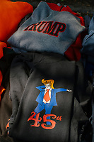 """A vendor displays pro-Trump hats, shirts, and other paraphernalia for sale as alt-right organization Super Happy Fun America demonstrates against facemasks, vaccines, and pandemic closures, and in support of the reelection of President Donald J. Trump near the residence of Massachusetts governor Charlie Baker in Swampscott, Massachusetts, on Sat., Sept. 26, 2020. Super Happy Fun America is most well known for organizing the Straight Pride Parade in Boston on August 31, 2019. Slogans and images on the shirts include """"God, Guns, and Trump"""" and an image of Trump performing the fad dance move dabbing."""