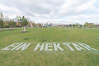 """Ministerialdirektor des Bundesministerium fuer wirtschaftliche Zusammenarbeit, Karin Kortmann (GIZ) und Entwicklung Gunther Berger und IAss-Exekutivdirektor Klaus Toepfer eroeffneten am Mittwoch den 22. April 2015 in Berlin die Installation """"EIN HEKTAR"""" mit symbolischer Versiegelung im Park am Gleisdreieck.<br /> Die Installation """"EIN HEKTAR"""" wird bis zum 25. Mai zu erleben sein. Ab dem 26.April, 16.00 Uhr, beginnt ein vielfaeltiges Begleitprogramm mit Performancekuenstlern, Filmen, Installationsobjekten und partizipativen Workshops, u.a. mit den Berliner Prinzessinnengaerten.<br /> """"EIN HEKTAR"""" wird durch die Sonderinitiative """"EINEWELT ohne Hunger"""" des Bundesministeriums fuer wirtschaftliche Zusammenarbeit und Entwicklung (BMZ) gefoerdert und gemeinsam mit der Deutschen Gesellschaft fuer Internationale Zusammenarbeit (GIZ), und dem Institute for Advanced Sustainability Studies (IAss organisiert. Die Flaeche im Park auf dem Gleisdreieck wird freundlicherweise von der Senatsverwaltung fuer Stadtentwicklung und Umwelt zur Verfuegung gestellt Die Installation """"Ein Hektar"""" bildet den Auftakt der Kampagne """"Boden. Grund zum Leben"""", die von BMZ, GIZ und einem breiten Partner-Netzwerk getragen wird und findet im Rahmen der vom IAss Potsdam und Partnern organisierten Global Soil Week 2015 statt.<br /> Im Bild: Aktionskuenstler versiegeln symbolisch 1ha Rasenflaeche.<br /> 22.4.2015, Berlin<br /> Copyright: Christian-Ditsch.de<br /> [Inhaltsveraendernde Manipulation des Fotos nur nach ausdruecklicher Genehmigung des Fotografen. Vereinbarungen ueber Abtretung von Persoenlichkeitsrechten/Model Release der abgebildeten Person/Personen liegen nicht vor. NO MODEL RELEASE! Nur fuer Redaktionelle Zwecke. Don't publish without copyright Christian-Ditsch.de, Veroeffentlichung nur mit Fotografennennung, sowie gegen Honorar, MwSt. und Beleg. Konto: I N G - D i B a, IBAN DE58500105175400192269, BIC INGDDEFFXXX, Kontakt: post@christian-ditsch.de<br /> Bei der Bearbeitung der Dateiinformat"""